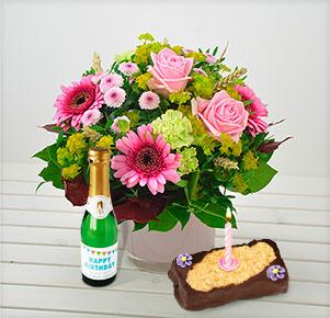 Pink Lady mit Geburtstagssekt und -törtchen